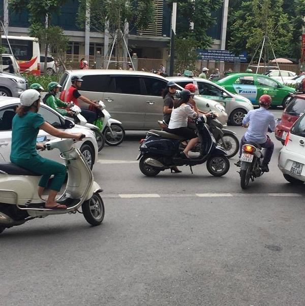 Người phụ nữ dừng xe giữa đường buôn điện thoại